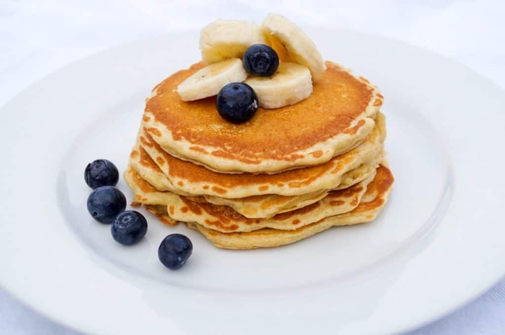 stack of pancakes topped with bananas and blueberries