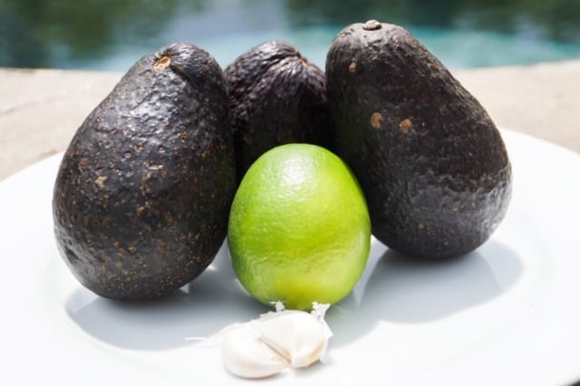 Three avocados, two cloves of garlic and one lime