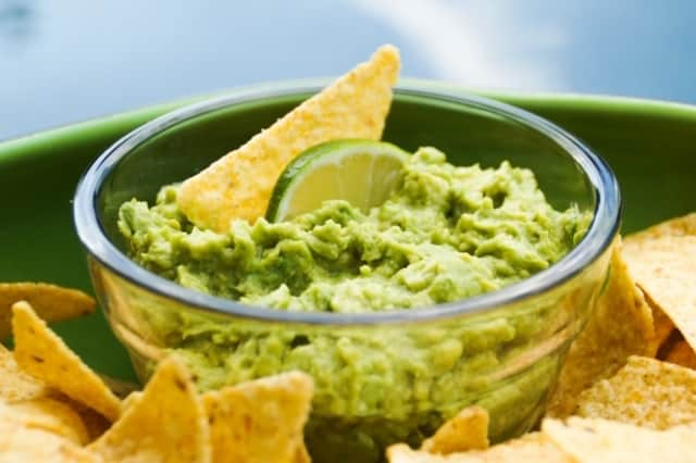 Bowl of guacamole surrounded by chips