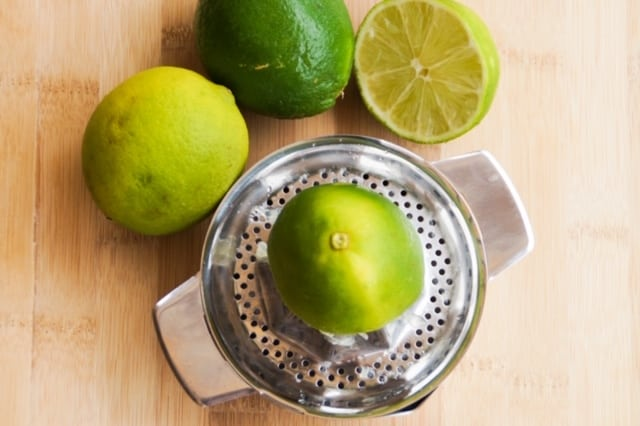 Lime on top of a stainless steel citrus juicer