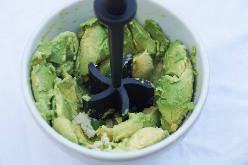 White bowl with avocados and a masher
