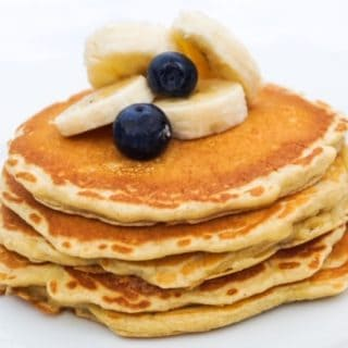 A stack of pancakes topped with banana slices and blueberries