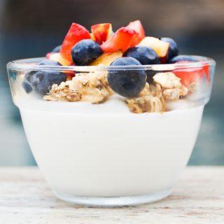 Yogurt, granola, and fruit layered in a glass bowl
