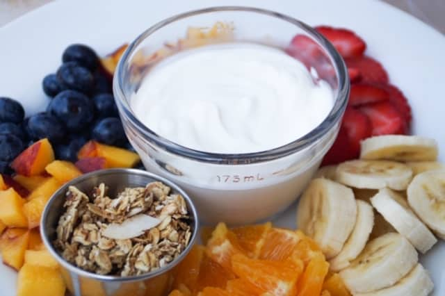 yogurt, granola and a variety of cut up fruits on a white plate