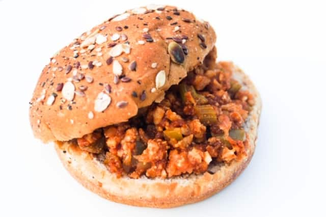 Sloppy Joe on a seeded bun on a white plate