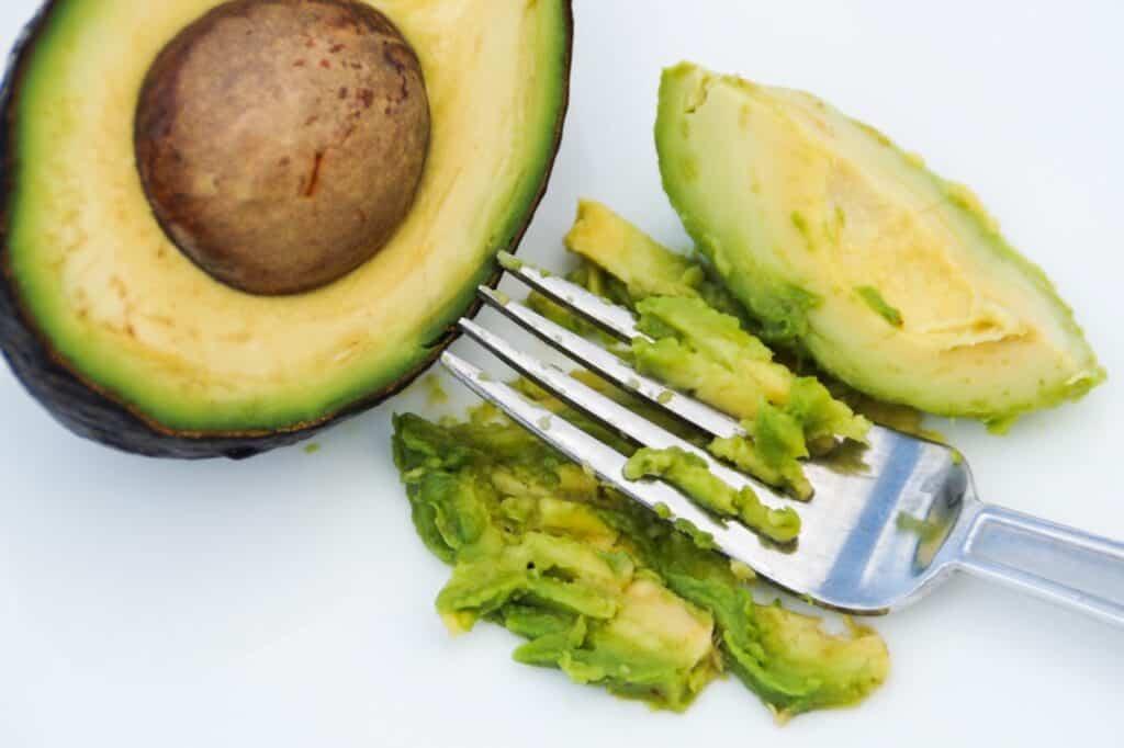 Half of an avocado next to avocado smashed avocado with a fork