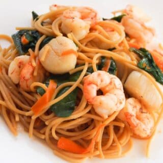 Asian noodle bowl with shrimp and scallops on a white plate