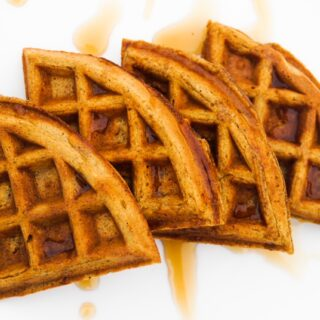 Pumpkin waffle quarters overlapping, topped with maple syrup