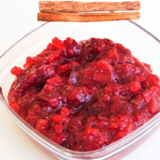 Cranberry sauce in glass dish with two cinnamon sticks