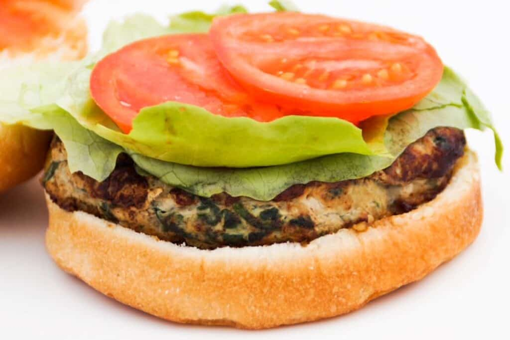 Open faced turkey burger with lettuce and tomato on a bun
