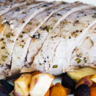 rosemary pork tenderloin, sliced and on a plate with tri-color carrots