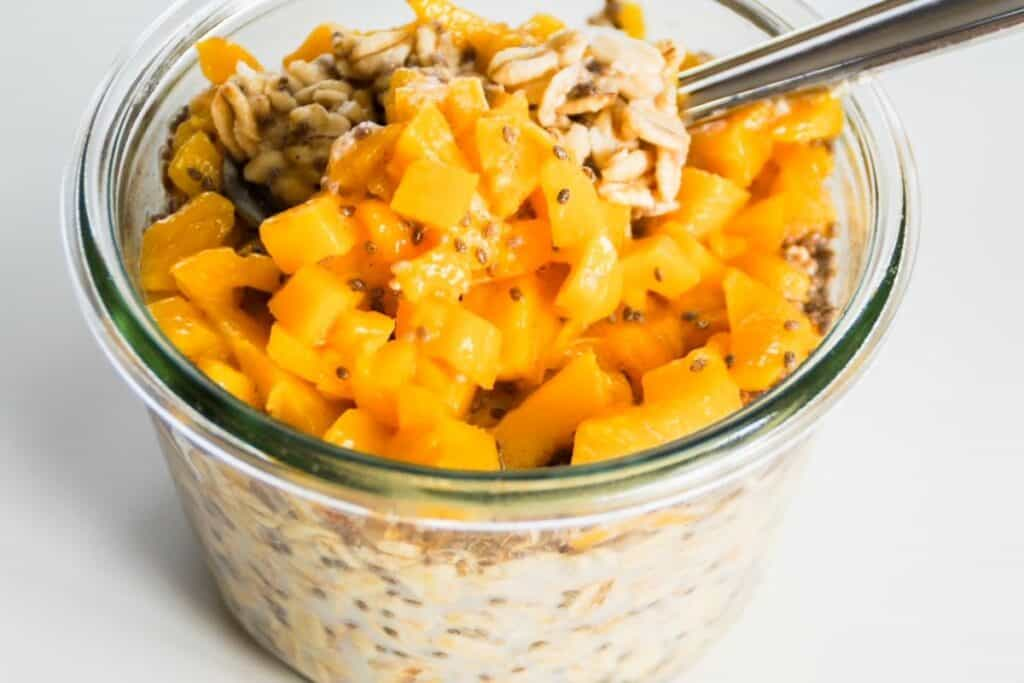 mango overnight oats in a jar with a spoon