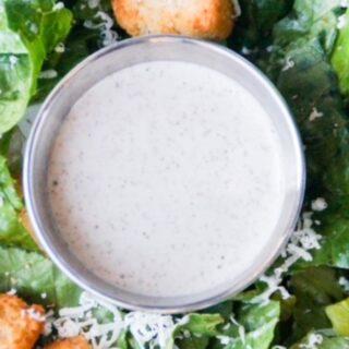 Caesar dressing in the center of a Caesar salad