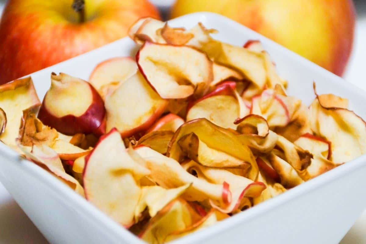 air fryer apple slices in a white square dish with apples in the background