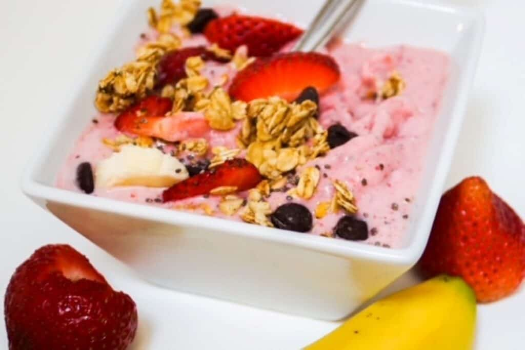 strawberry banana smoothie bowl with toppings in a square white bowl