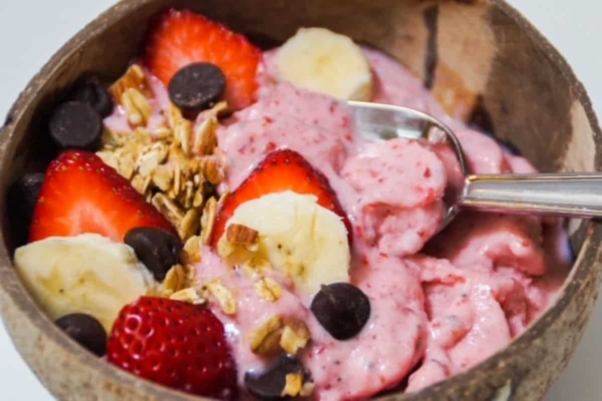 strawberry banana smoothie bowl in a coconut shell bowl with toppings
