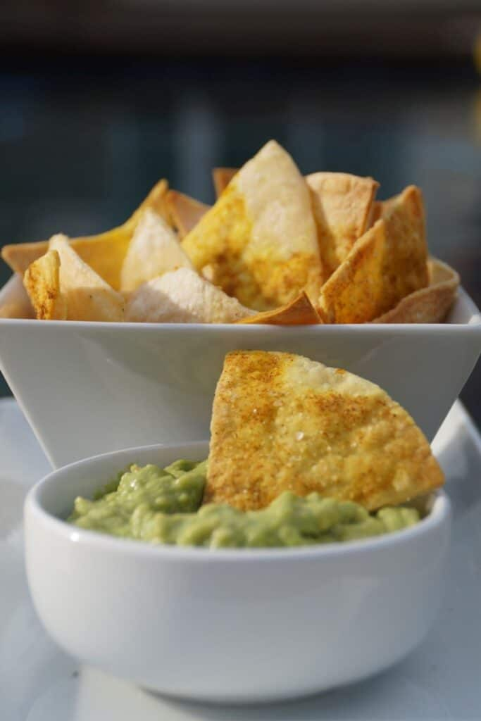 tortilla chip in a bowl of guacamole with a bowl of chips in the background