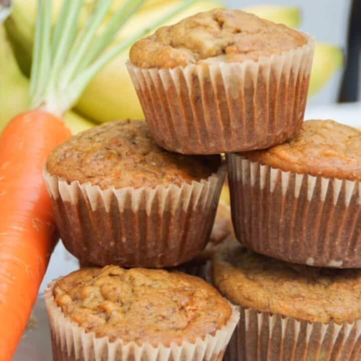 stack of banana carrot muffins with a carrot on the side and bananas in the background