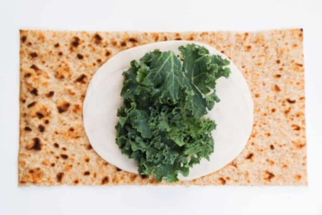 open flatbread topped with one slice of chicken and a small handful of kale
