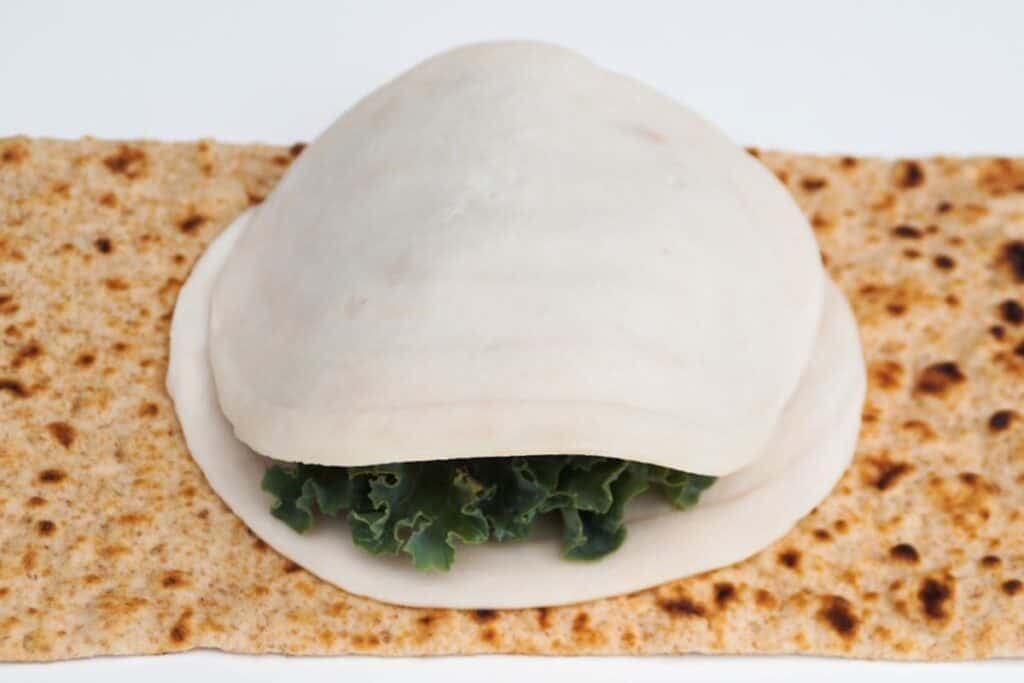 flatbread laid out topped with once slice of turkey, kale, and a second slice of turkey