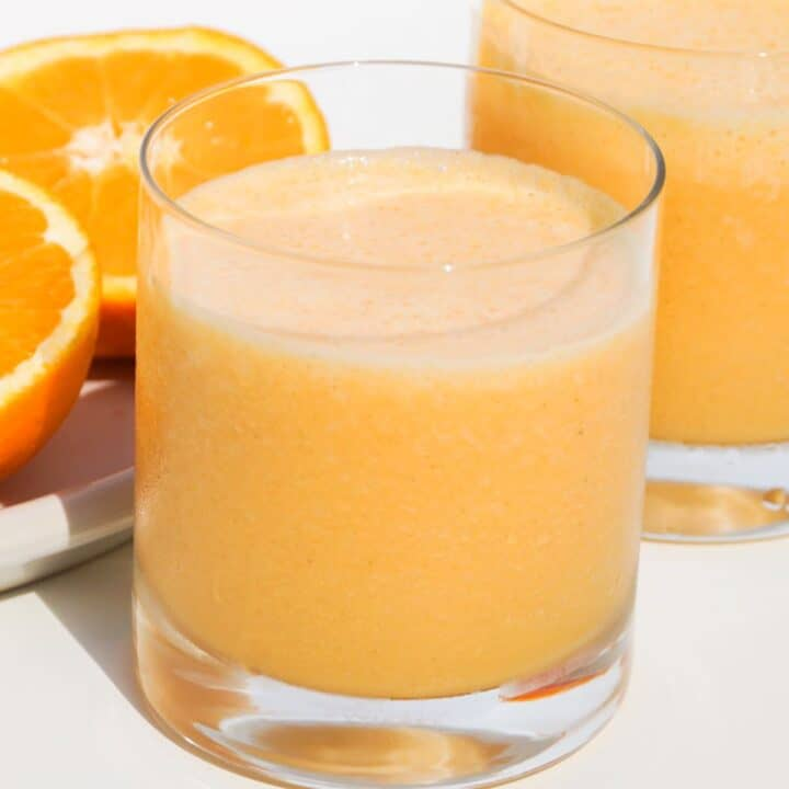 two glasses of orange carrot smoothie with a freshly sliced orange