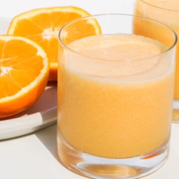 two glasses of orange carrot smoothie with two halves of a fresh orange